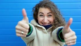 Härlig ung lockig kvinna som visar tumme upp två och ler, nära den blåa väggen lager videofilmer