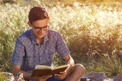 Härlig ung lycklig grabb med exponeringsglas som läser utomhus en bok på en solig dag arkivbild