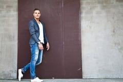 Härlig ung man utomhus mot en vägg royaltyfri foto