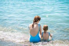 Härlig ung moder och dotter som har gyckel som vilar på havet De sitter i vattnet i den samma baddräkten, deras baksidor i royaltyfria bilder
