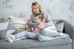 Härlig ung moder och hennes lilla dotterklockafilmer tillsammans, lek på minnestavlan och att jubla att sitta på soffan Mammakram fotografering för bildbyråer