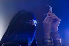 Härlig ung muslimflicka som rymmer ett månesymbol, andlighet royaltyfri bild