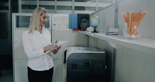 Härlig ung printing för affärskvinna i kontoret lager videofilmer