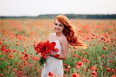 Härlig ung rödhårig kvinna i vallmofält med flyghår Royaltyfria Bilder