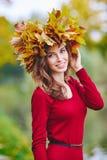 Härlig ung rödhårig mankvinna med en krans av sidor på hennes huvud Arkivfoton
