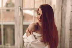 Härlig ung rödhårig mankvinna med långt hårsammanträde på windowsil royaltyfria bilder