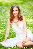 Härlig ung rödhårig mankvinna på äng med vita blommor Arkivfoto