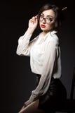 Härlig ung sexig affärskvinna med mörkt updohår som ser direkt över hennes moderiktiga exponeringsglas i modern ram royaltyfri foto