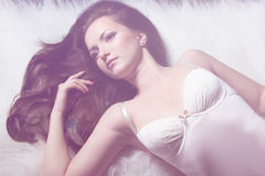 Härlig ung sexig flickabrunett med makeup i den vita bodysuiten i studion på en svart bakgrund Royaltyfri Foto