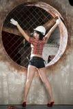 Härlig ung sexig kvinna i en vit hjälm som poserar med konstruktionsutrustning royaltyfria foton