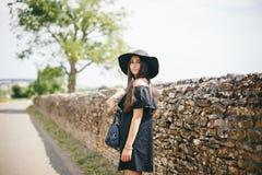 Härlig ung sexig kvinnamodell av brunetten med mörk hud i den svarta klänningen och hatten med fält, fashionably klätt anseende i arkivbilder