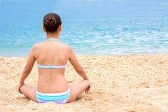 Härlig ung strand för hav för sommar för meditation för yoga för tonåringflickaövning royaltyfria foton