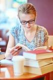 Härlig ung student med massor av böcker Arkivbilder