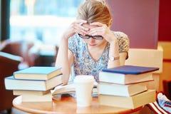 Härlig ung student med massor av böcker Arkivfoto