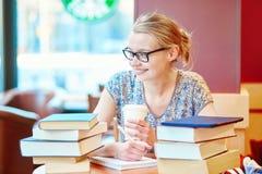 Härlig ung student med massor av böcker Royaltyfria Bilder
