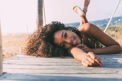 Härlig ung svart kvinna som ner ligger i en träfotbro Arkivbilder
