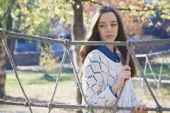 Härlig ung tonårs- flicka som poserar nära ett repstaket Royaltyfri Bild