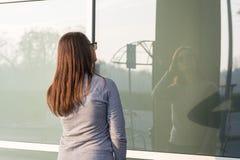 Härlig ung tonårs- le flicka som framme poserar av det glass fönstret Royaltyfri Bild