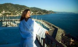 Härlig uppdiktad kvinna i en vit badrock nära bada på terrassen av ett lyxigt hotell Royaltyfri Foto