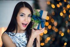 Härlig upphetsad le ung kvinna med den närvarande gåvan som känner det lyckliga near julträdet Det lyckliga ung flickainnehav hän Royaltyfri Foto