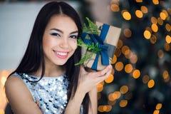 Härlig upphetsad le ung kvinna med den närvarande gåvan som känner det lyckliga near julträdet Det lyckliga ung flickainnehav hän Fotografering för Bildbyråer