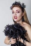 Härlig uppnosig flicka i bilden av en vampyr med ljus mörk makeup, den svarta vampyrbruden med en bukett och en svart krans Royaltyfria Foton