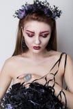 Härlig uppnosig flicka i bilden av en vampyr med ljus mörk makeup, den svarta vampyrbruden med en bukett och en svart krans Arkivbilder
