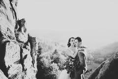 Härlig ursnygg brud som poserar för att ansa och har gyckel, lyxig ceremoni på berg med den fantastiska sikten, utrymme för text royaltyfria foton