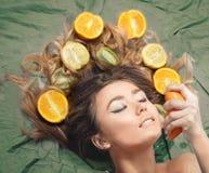 Härlig ursnygg modellflicka med färgrika citrusa sunda frukter i hennes skinande hår Omsorg och hårprodukter Begrepp för håromsor Arkivfoton