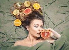 Härlig ursnygg modellflicka med färgrika citrusa sunda frukter i hennes skinande hår Omsorg och hårprodukter Begrepp för håromsor Fotografering för Bildbyråer