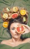Härlig ursnygg modellflicka med färgrika citrusa sunda frukter i hennes skinande hår Omsorg och hårprodukter Begrepp för håromsor Royaltyfria Bilder