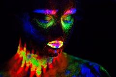 Härlig utomjordisk modellkvinna i neonljus Det är ståenden av den härliga modellen med det fluorescerande sminket, konst Arkivfoto