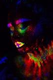 Härlig utomjordisk modellkvinna i neonljus Det är ståenden av den härliga modellen med det fluorescerande sminket, konst Fotografering för Bildbyråer