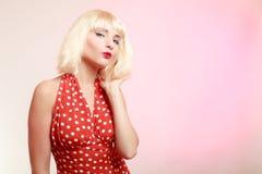 Härlig utvikningsbrudflicka i blond peruk och retro röd klänning som blåser en kyss. Royaltyfri Foto