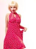 Härlig utvikningsbrudflicka i blond peruk och retro röd klänningdans. Parti. Royaltyfria Bilder