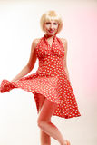 Härlig utvikningsbrudflicka i blond peruk och retro röd klänningdans. Parti. Arkivbild