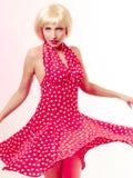 Härlig utvikningsbrudflicka i blond peruk och retro röd klänningdans. Parti. Royaltyfri Bild