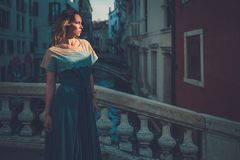 Härlig välklädd kvinna som poserar på en bro över kanalen i Venedig Royaltyfri Foto