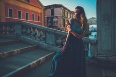 Härlig välklädd kvinna som poserar på en bro över kanalen i Venedig Arkivfoto