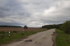 Härlig vårskog och grusväg i de mellersta Uralsna Arkivfoton