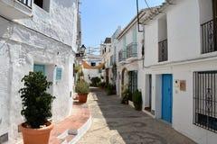 Härlig vandringsled i Frigiliana med utmärkt dekorerade trottoar och påfyllningar av växter, Frigiliana - spansk vit by Andalusia Arkivfoto
