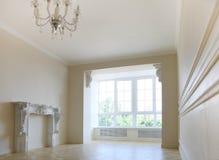 Härlig vardagsrum i ljus tonar med det stora fönstret Arkivbilder