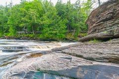 Härlig vattenfall på delstatsparken för ett piggsvinbergvildmark i övrehalvön av Michigan - slät stillsam flödande wate fotografering för bildbyråer