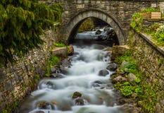 Härlig vattenfall under en bro Arkivbild