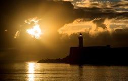 Härlig vibrerande soluppgånghimmel över det lugna vattenhavet med lightho royaltyfri fotografi