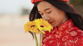 Härlig vietnamesisk flicka i den röda traditionella klänningen Ao Dai med gula blommor Närbild stock video
