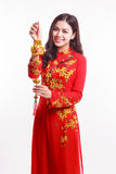 Härlig vietnamesisk kvinna med röd ao dai som rymmer den lyckliga prydnaden för nytt år - bunt av guld Royaltyfria Bilder
