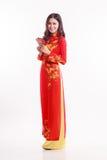 Härlig vietnamesisk kvinna med röd ao dai som rymmer det röda paketet Arkivfoton