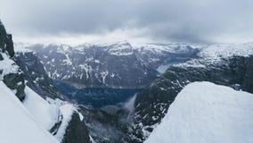 Härlig vinterbergpanorama i Norge, på vägtoTrolltungaen Den fantastiska blåa sjön mellan höjdpunkten vaggar under snö arkivfoto