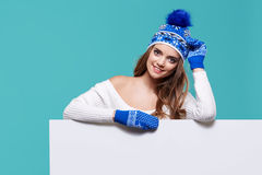 Härlig vinterkvinna som rymmer en tom affischtavla Royaltyfri Foto